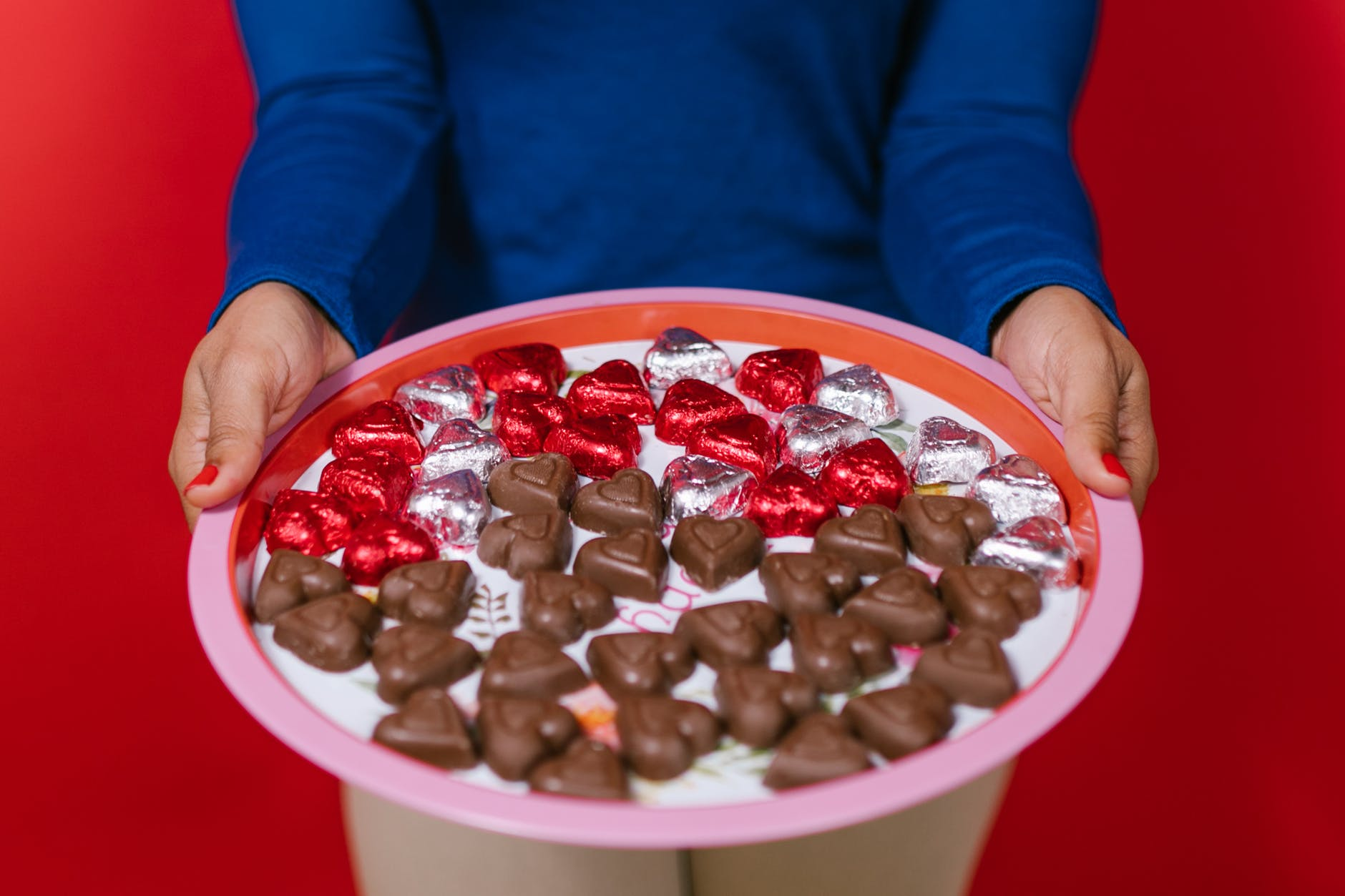 A lady with a blue top holding a tray filled with lots of small heart-shaped milk chocolates.  Some are wrapped with a silver or a red paper