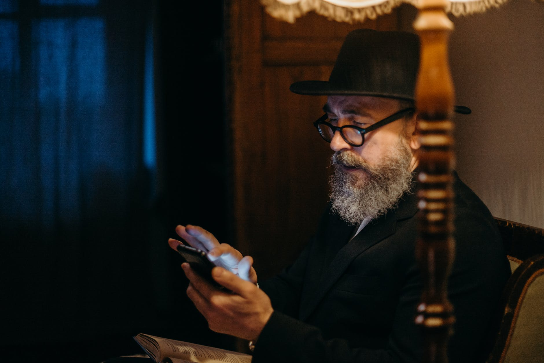 A gentle man with bare wearing a black hat is sitting, checking his mobile phone.