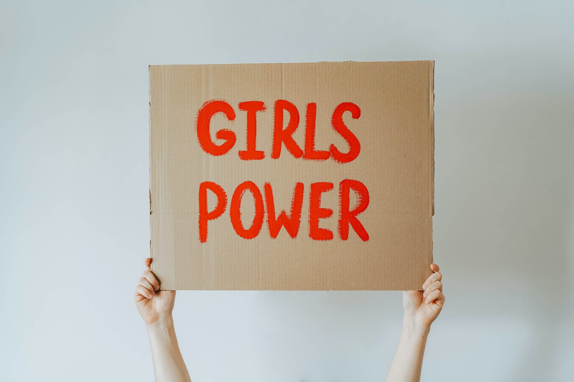 "A female holdS""GIRLS POWER"" board"
