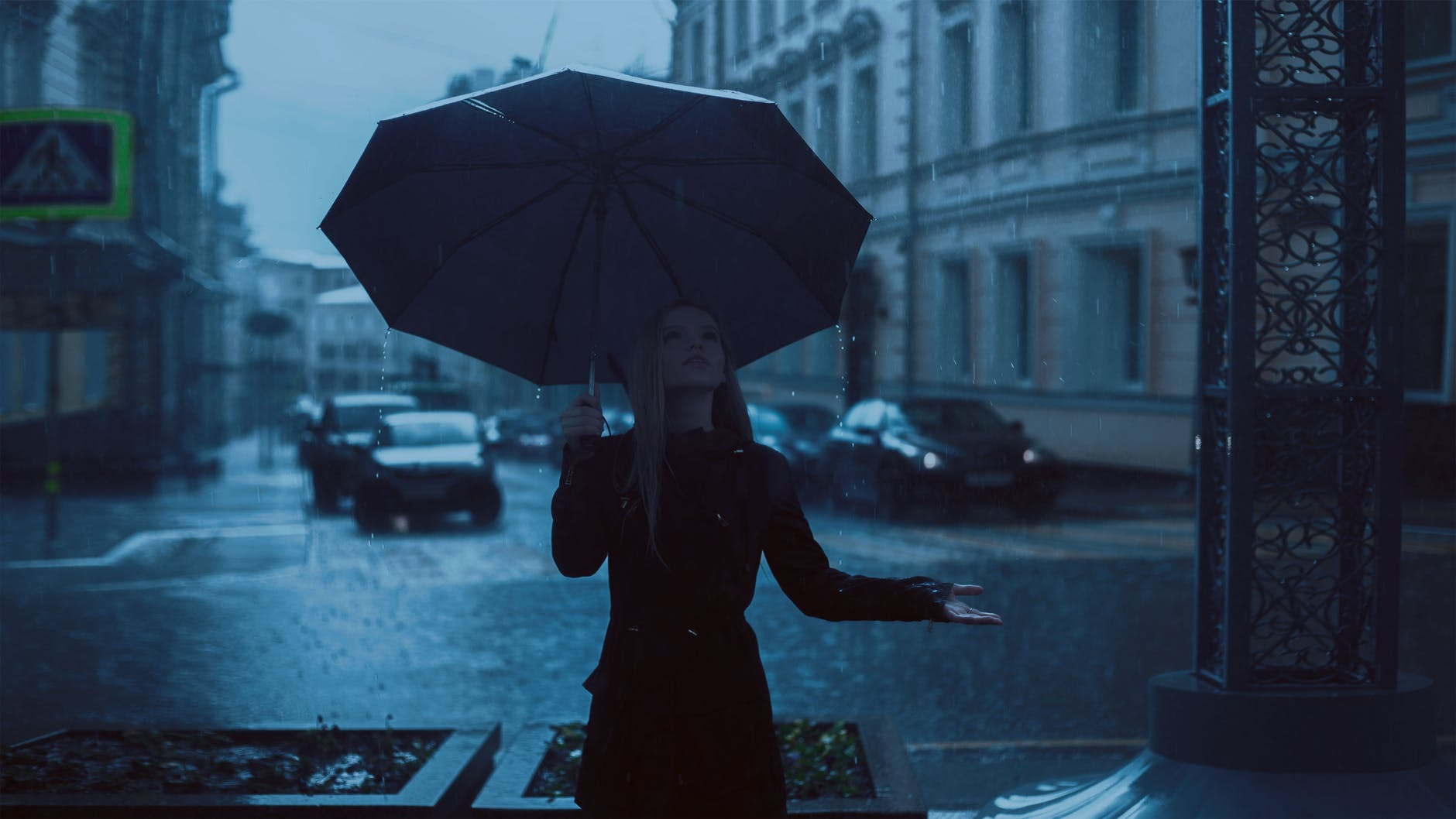 A lady is standing holding an umbrella on her right hand and opening her left hand to feel the rain